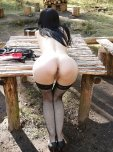 amateur photo Bending over on a wooden table outside