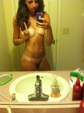 amateur photo Cute girl in the mirror with tan lines