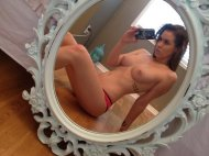 Topless brunette in the mirror