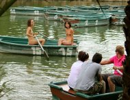 Happy embarrassed naked girls enjoying a leisurely ride in a rowboat