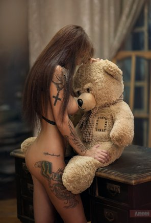 amateur photo Hot girl with some awesome ink hugging a teddybear wearing a scarf