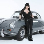 amateur photo Hitomi posing next to a classic car