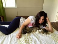 beautiful brunette in leggings with the perfect figure laying next to her cat.