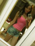 amateur photo This brunette girl, taking a selfie in the bathroom, is hot and has nice cleavage. She has blue nails, a tattoo, and is wearing a pink shirt and jean