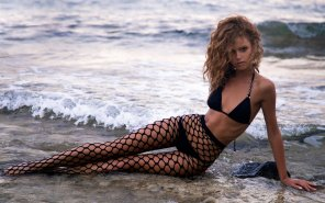 amateur photo beautiful babe with a smoking hot body poses in fishnet stockings in the surf