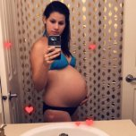 Pregnant girl brunette takes a picture of herself on a smartphone in front of a mirror