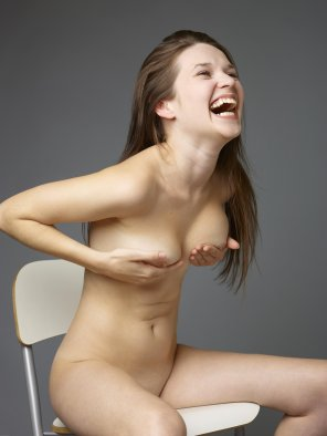 amateur photo Happy naked brunette awkwardly laughing with her sexy handbra