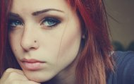 Red hair, blue eyes, nose piercing, intense look.
