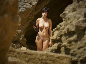 amateur photo Naked MILF brunette with glasses among the rocks
