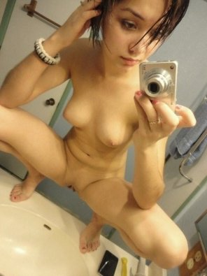 amateur photo Short haired babe takes a nude selfie sitting on the sink.