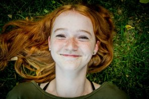 amateur photo Happy redhead on the grass