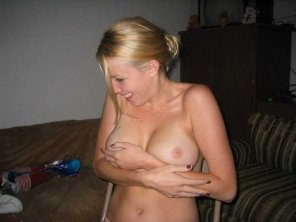 amateur photo Awkwardly laughing while trying to cover her boobs