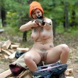 Girl sitting on a log with her pants pulled down, wearing a beanie, and aiming a gun. Also, boob tattoos.