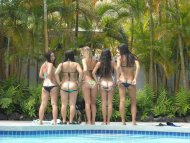 Cute chicks mooning by the swimming pool