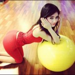 amateur photo Black-Haired beauty leaning over exercise ball.