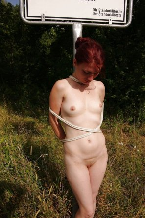 amateur photo German girl tied up to a street sign.