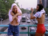 Two cute embarrassed girls flashing their boobs on a bridge