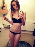 amateur photo Babe with a gorgeous body, and a guitar on the wall.