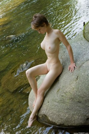 amateur photo Short hair pale girl sitting over a rock near the river