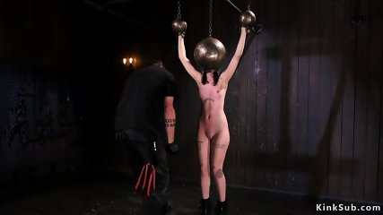 Shaved slut with hands and head in metal balls