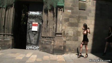 Brunette in metal shackles in public