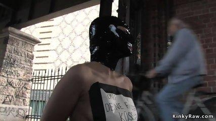 Naked masked blonde kneeling in public